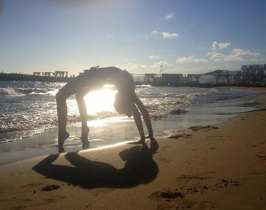 Na pláži dělá gymnastické cviky.