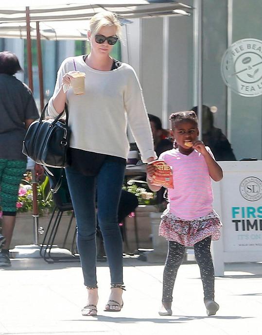Herečka na procházce se synem, oblečeným v dívčích šatech.