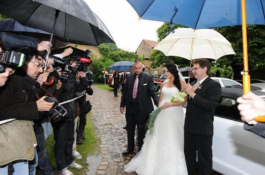 Před tvrzí stály davy novinářů. Nevěstu vede její otec.