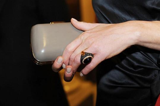 Prsten s barevnými diamanty a onyxem a lakovaná kabelka Balenciaga.
