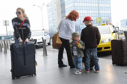 Simonina rodina právě dorazila na Letiště Václava Havla a vykládá své značkové kufry.