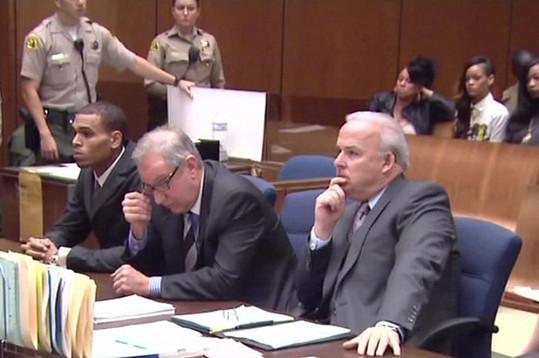 Chris u soudu kvůli napadení Rihanny, která sedí v pozadí.