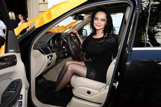 Spíš než na místě řidiče sedí na zadním sedadle.