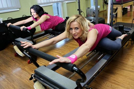 Terezie Kašparovská a Bára Kozáková se při cvičení podporují.