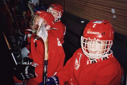 Tady Nasty sedí na střídačce a chlapeček vedle něj s helmou, která připomíná akvárium, je Roman Červenka.