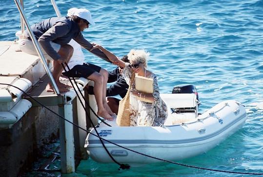 Dva pracovníci hotelu pomáhají herečce ze člunu.