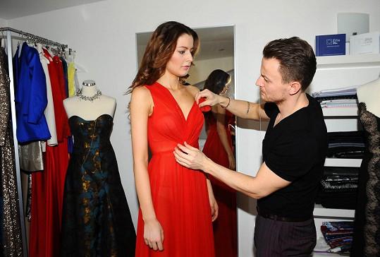 Návrhář upravuje šaty přímo na modelce.