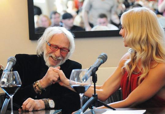 Taťána v rudých šatech a Pierre s brýlemi s rudými obroučky na tiskové konferenci.