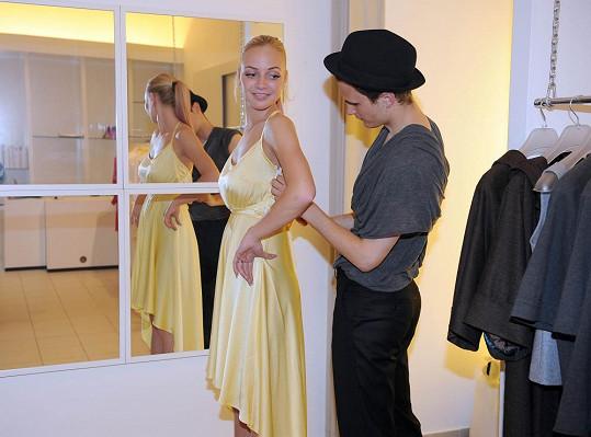Návrhář pomáhá zpěvačce do šatů.