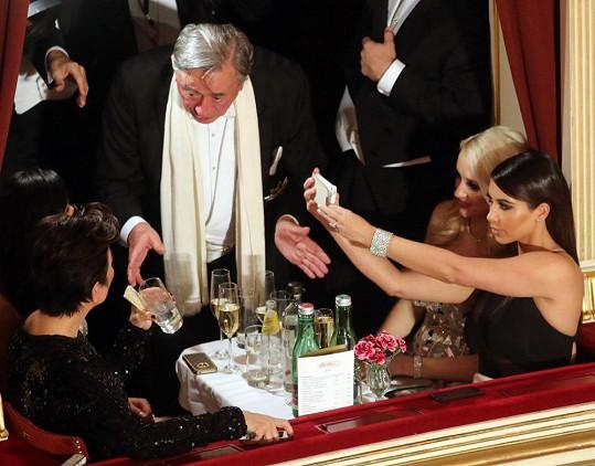 Kim v lóži s matkou Kris (sedící naproti ní) a Richardem Lugnerem, který je za tučný honorář pozval.