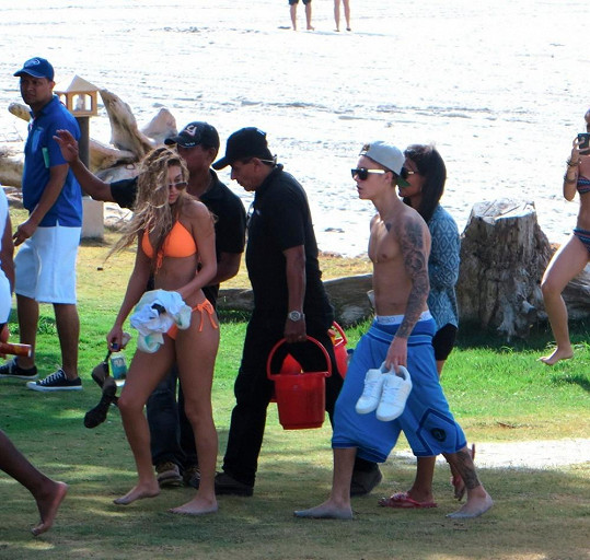 Popová hvězdička s přítelkyní obklopená početnou skupinkou svých nohsledů.