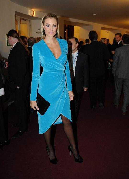 Zavinovací šaty z tyrkysového sametu si navrhla Kateřina Průšová sama a ušila jí je kamarádka. Barevně výrazný model chytře doplnila černými punčocháči, nenápadným psaníčkem YSL a botami Prada.
