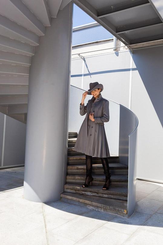 Gábina v plisovaném kabátku a klobouku s esovitou krempou v mušketýrském stylu.