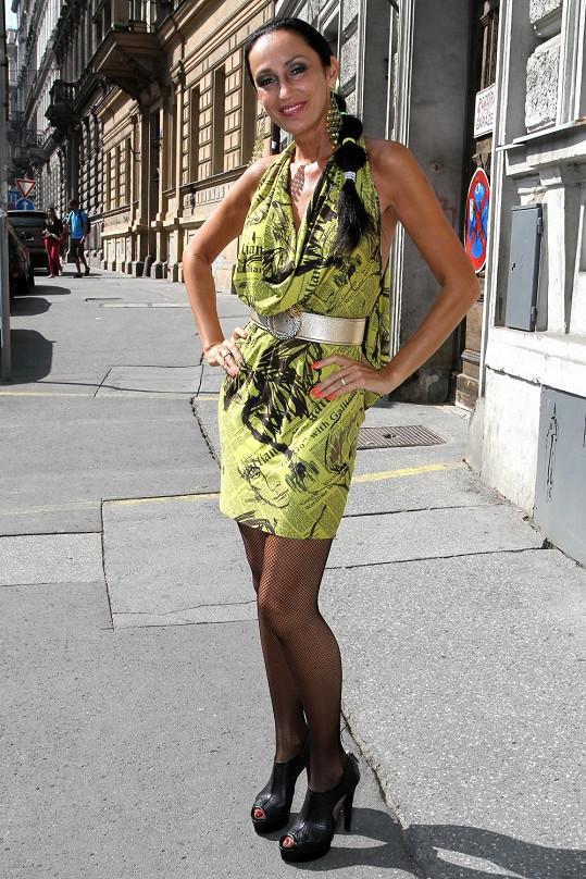 Mini šaty s novinovým vzorem John Galliano jsou natolik výrazné, že neunesly další doplňky, jako je metalický pásek, visací náušnice, síťované punčochy a laškovný vlasový styling.