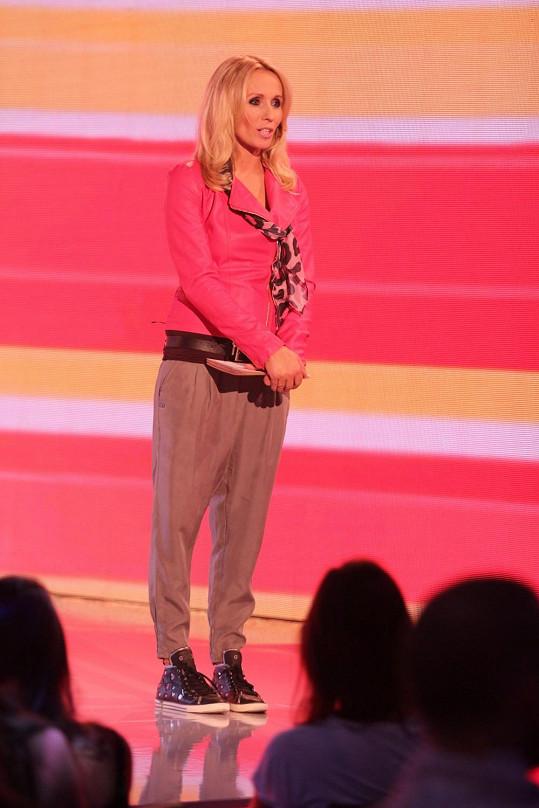Růžový křivák zdobený hedvábným šátkem s kočičím vzorem a k tomu tenisky. Některé outfity moderátorky dostávají jasný palec dolů.