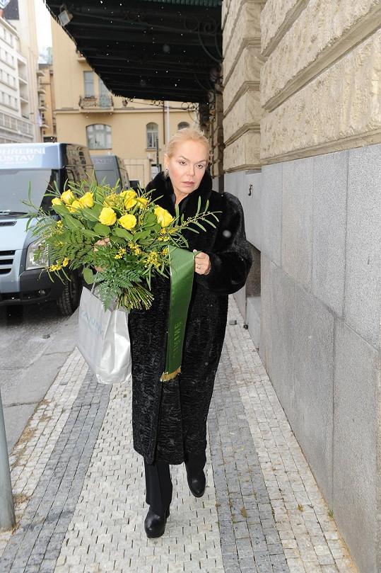 Dagmar Havlová vypadá hodně zdrceně. Přinesla kytici žlutých růží.