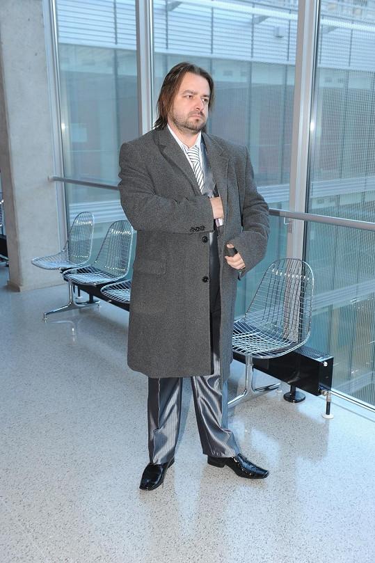 """Zdeněk Macura se na dnešní jednání vyfešákoval. Oblékl si """"božhodový"""" lesklý oblek, přes který přehodil dlouhý kabát."""