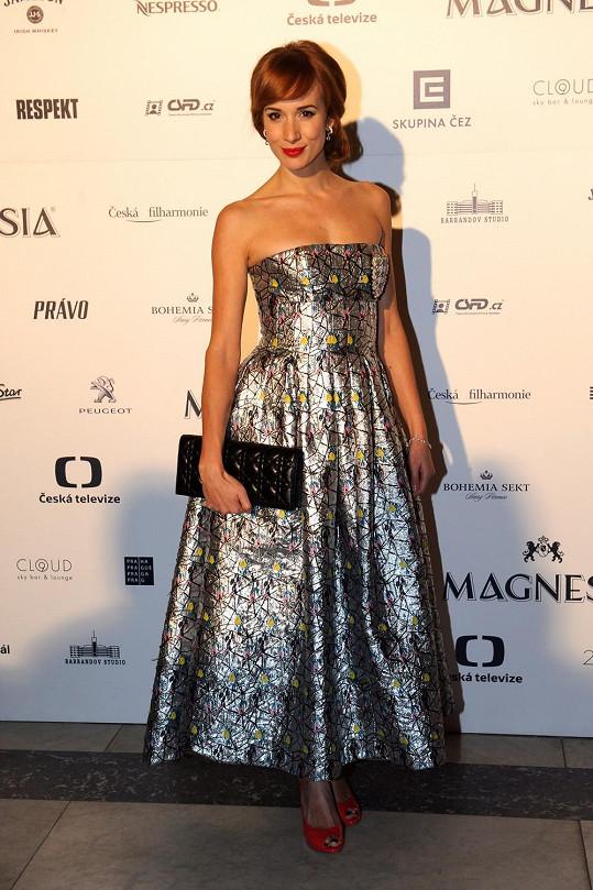 U Diora si slovenská herečka Táňa Pauhofová vybrala metalickou róbu bez ramínek s nabíranou sukní. Model sladila s psaníčkem s ikonickým vzorem cannage a kontrastními lodičkami v oranžové barvě s otevřenou špičkou.