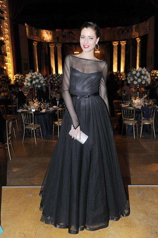 Velmi se nám líbí, jak jsou klasické černé šaty s kolovou sukní přetaženy stejně barevným tylem, který je u rukávů zakončený efektním propínáním a u sukně lesklým lemem korespondujícím s páskem.