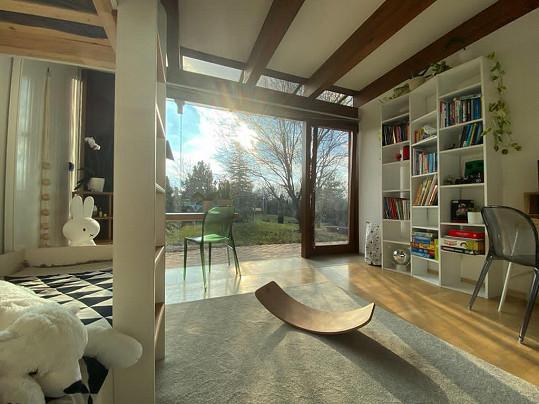 Prostorný obývací prostor s velkými okny vedoucími na zahradu.