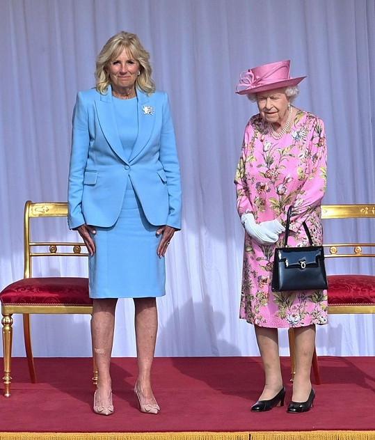 Při setkání s Jill Bidenovou na sobě měla Alžběta II. světle růžové šaty s výrazným vzorem. Ty doplnila bílými rukavičkami a perlovým náhrdelníkem, který nosí téměř pokaždé.