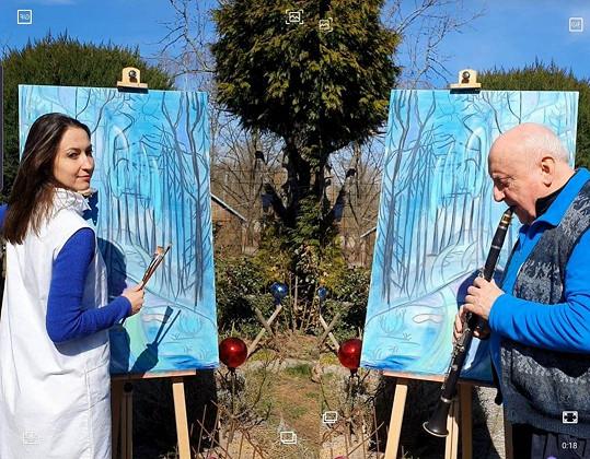 Zatímco Lucie na zahradě chalupy maluje, Felix jí k tomu hraje.
