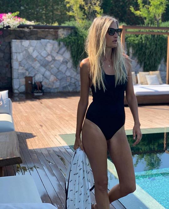 V plavkách u bazénu v resortu, který spoluvlastní s manželem.