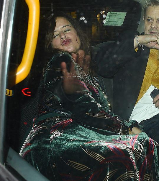 Z taxíku pod dohledem manžela fotografům posílala polibky.