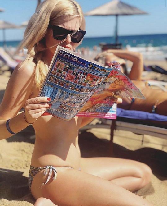 Nikol se na pláži bavila nad retro časopisy.