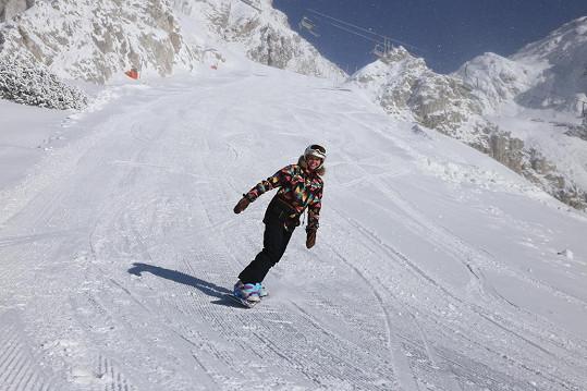 Patricie brázdí svahy na snowboardu.