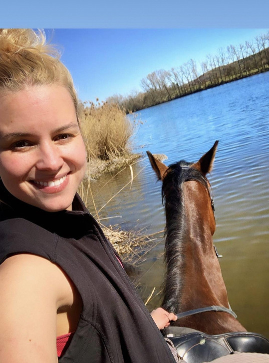 Patricie s koněm u rybníka. Sledující jí vyčetli, že nemá helmu.