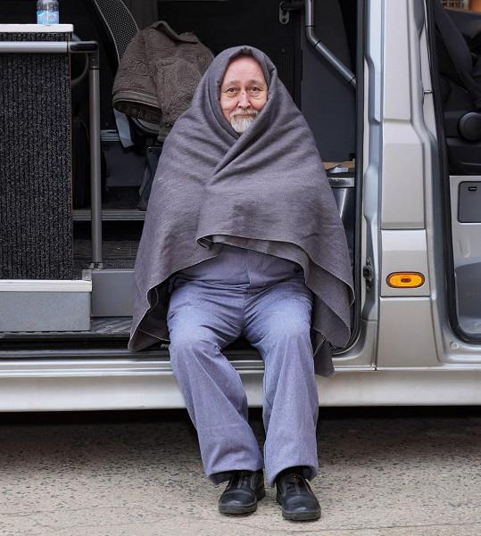 Během čekání na záběr se zahříval pod dekou.