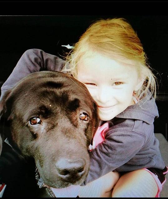 S láskou vzpomíná i na předchozího parťáka, černého labradora Santina. Na snímku s Milošovou dcerou Adinou.