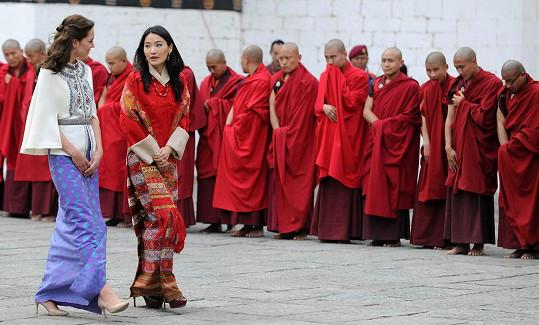 Obě dámy před klášterem s mnichy v pozadí