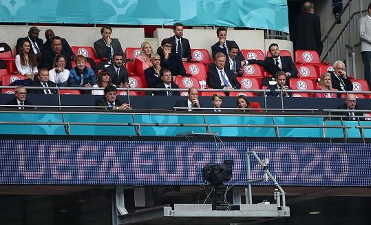 Tribuna plná hvězd. Královská rodina v popředí a za nimi David Beckham se synem Romeem, vedle nich sedí Ed Sheeran s manželkou Cherry, za nimi bývalý anglický brankář David Seaman a kousek od něj zpěvačka Ellie Goulding s manželem Casparem.