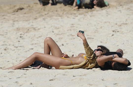 Její přítel se do plavek nesvlékal, ale selfíčka si na pláži pořídili.
