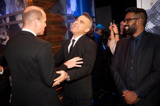 Výtěžek z večera poputuje na pomoc lidem ze zábavního průmyslu, kteří ji potřebují ať už v důsledku věku, nemoci či jiných sociálních problémů. Na snímku princ William, zpěvák Robbie Williams a komik a herec Romesh Ranganathan.