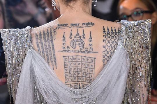 Výstřih na zádech ukázal její tetování.