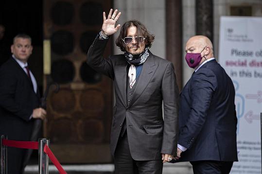 Johnny Depp sice fanouškům mával také, ale rozhodně se neusmíval.