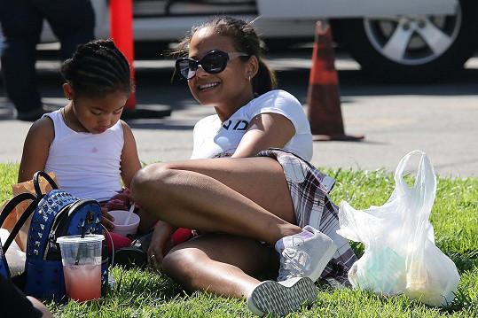 Sympatická maminka s pětiletou dcerou si udělaly pohodlí na trávníku u farmářských trhů.