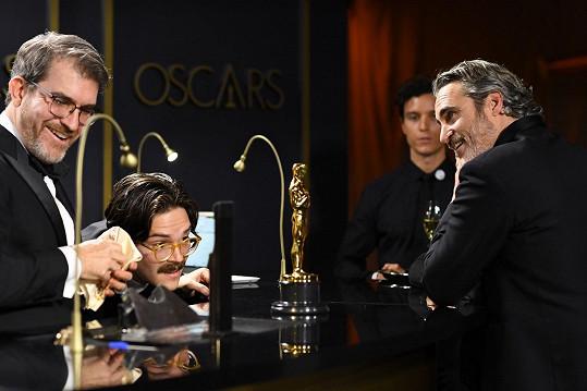 Nebývale usměvavý a spokojený Joaquin Phoenix u stejného pultu u rytců