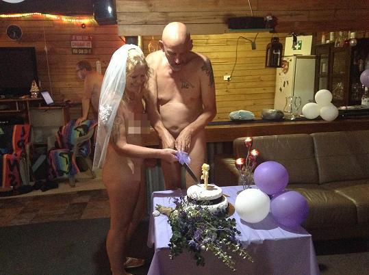 Ženich s nevěstou rozkrajují svatební dort.