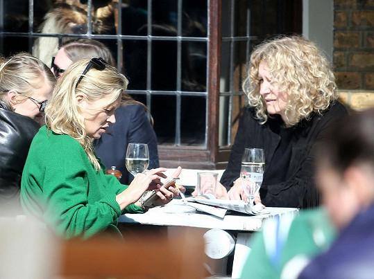Modelka poseděla s přáteli u skleničky vína.