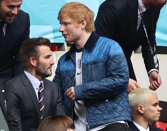 Ed Sheeran procházející na tribuně kolem Davida Beckhama a jeho syna Romea.