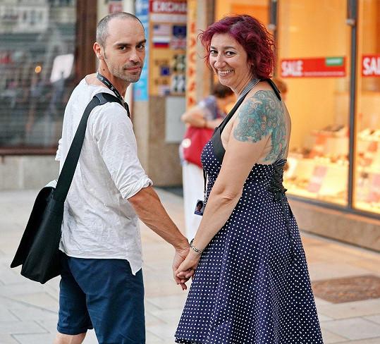 Pár si užívá kolonádu s úsměvy a ruku v ruce.