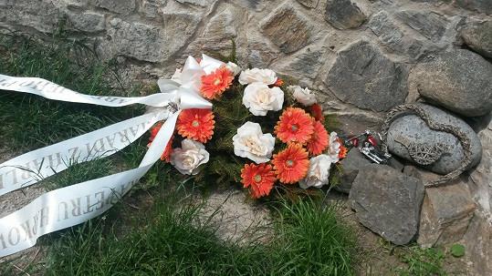 U hřbitovní zdi leží věnec od kamarádů motorkářů a malinká motorka.
