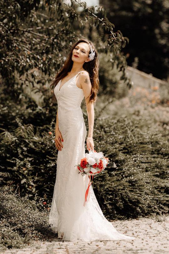 Nevěsta zvolila obepnuté šaty, květinovou ozdobu do vlasů a rtěnku sladila s kyticí rudých a bílých růží.