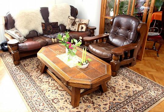 Obýváku dominuje kožená pohovka a masivní stůl.