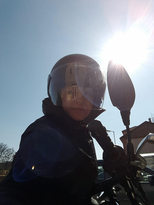Hybnerová brázdí pražské silnice na mopedu.