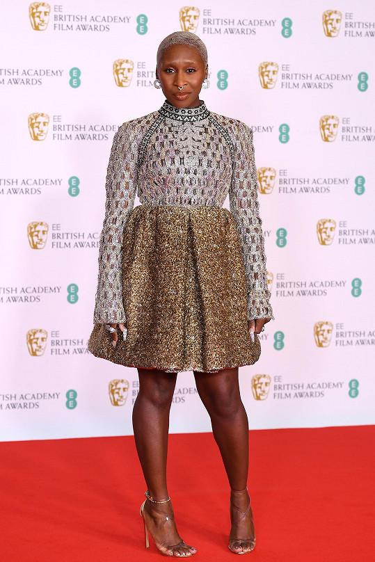 Status módní ikony si opět potvrdila Cynthia Erivo ve stříbrnozlatých šatech Louis Vuitton. Kombinace dlouhých rukávů a nabírané sukně nad kolena působí dokonale.
